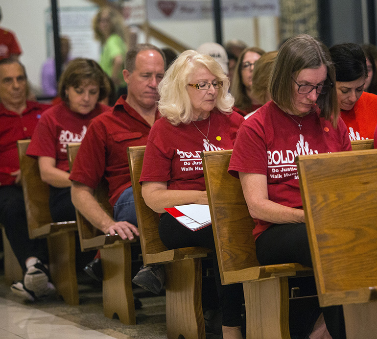 Members of St. Paul Lutheran Church, Weston, bow their heads as Archbishop Thomas Wenski leads the congregation in an opening prayer at BOLD Justice's 11th annual Nehemiah Action assembly, held April 23 at St. David Church in Davie.