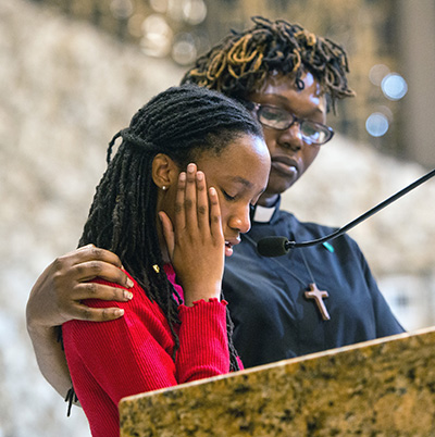 Rev. Andrea Byer-Thomas, of Village United Methodist Church in North Lauderdale, comforts her daughter, Arleigha Byer, 15, as she testifies at BOLD Justice's 2018 Nehemiah Action assembly about her friend Gina Montalto, who belonged to the same Girl Scout troop and was killed at Marjorie Stoneman Douglas High School.