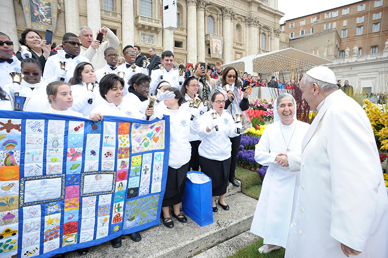 A very excited Sister Filomena Mastrangelo greets Pope Francis during the general audience at St. Peter's Square April 4 as members of the Marian Center hand bell choir ring their bells and hold the quilt they presented to the pope.