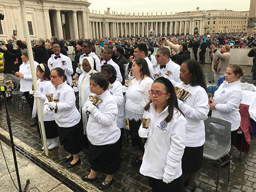 Marian Center hand bell musicians await the start of their performance at St. Peter's Square on April 4.