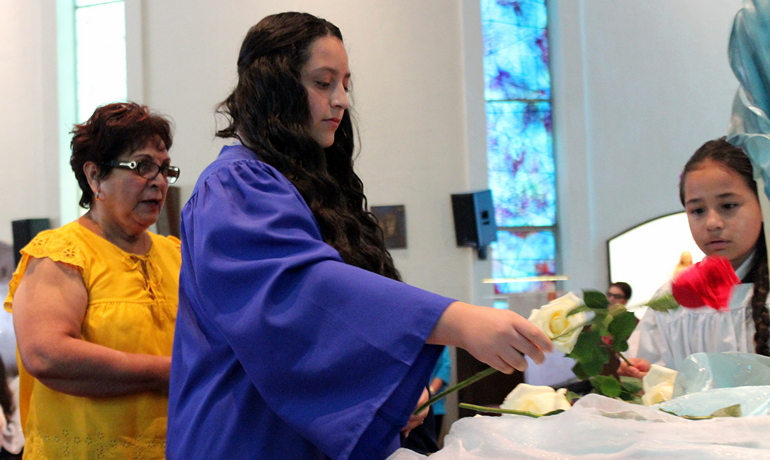 Hailey Sabillon lays a rose before an image of Mary during a Mother's Day Mass at St. Michael the Archangel. Taking part are altar server Ana Ghisays, right, and a grandmother from St. Michael's School. Both girls attend the school.