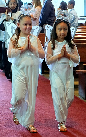 Students Aubrey Sabillon and Alanis Gamarra dress as angels for a Mother's Day Mass at St. Michael the Archangel. Both attend St. Michael's School.