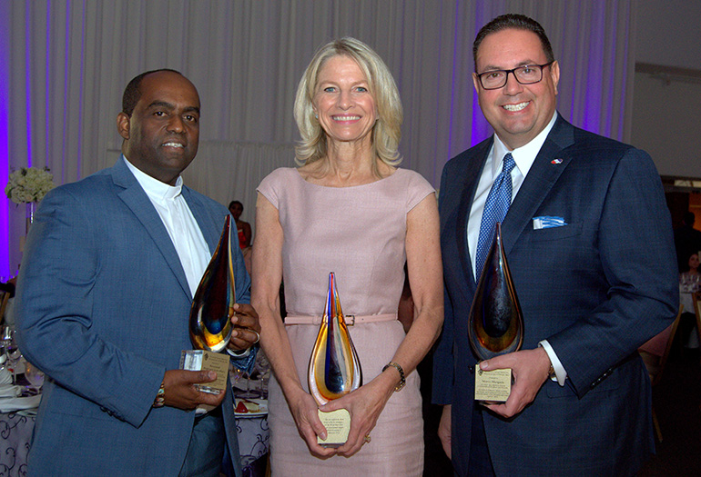 The three honorees show their New American Awards at the 20th anniversary gala for Catholic Legal Services in Miami on April 27. From left are Father Reginald Jean-Mary of Notre Dame d'Haiti Church; Julie Grimes, managing partner for a hotel chain; and Mario Murgado, CEO of a Miami-based auto dealership.