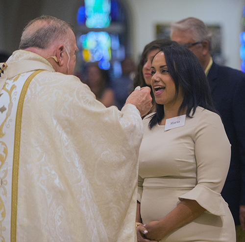 A candidate receives her first Communion from Archbishop Thomas Wenski during the second of two Rite of Reception ceremonies April 29 at St. Mary Cathedral.