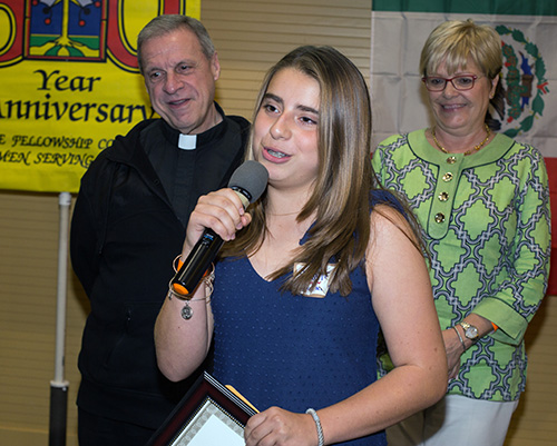 Daniela Hoyos, 13, thanks the Men's Club for her scholarship as Msgr. Pablo Navarro, St. John Neumann's pastor, and Maria Elena Villas, school principal, look on.