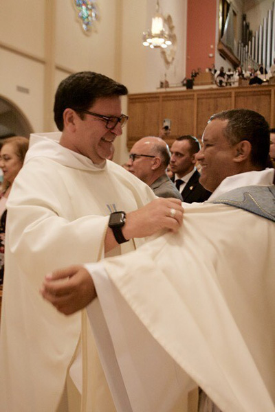 Father Jimmy Acevedo, left, helps vest his former parishioner at Mother of Our Redeemer, newly ordained Father Gustavo Barros.