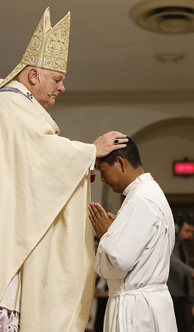 Archbishop Thomas Wenski lays hands on Deacon Juan Alberto Gomez, calling down the Holy Spirit and ordaining him a