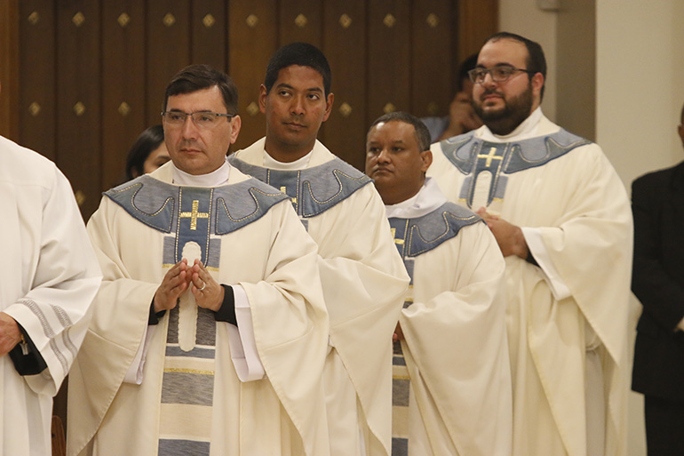 Newly ordained priests return to take their place in the sanctuary after having their hands anointed with oil of chrism. From left: Fathers Omar Ayubi, Juan Alberto Gomez, Gustavo Barros and Matthew Gomez.