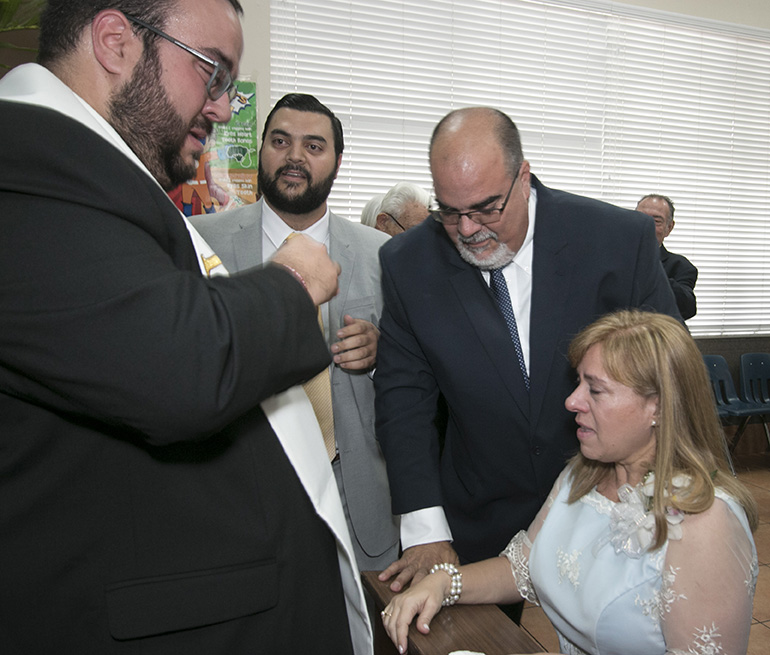 At the cathedral hall after the ceremony, Father Matthew Gomez wipes away tears after giving one of his first blessings to his parents, Fernando and Laura Gomez, as his brother Mark looks on.