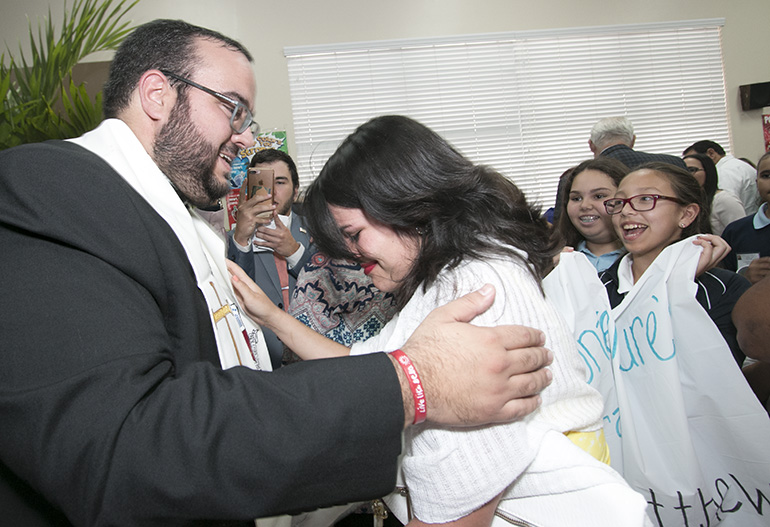 At the cathedral hall after the ceremony, Father Matthew Gomez gives one of his first blessings to Rebecca Garcia, current coordinator of Encuentros Juveniles, as fifth-graders from St. Bonaventure School in Davie, who