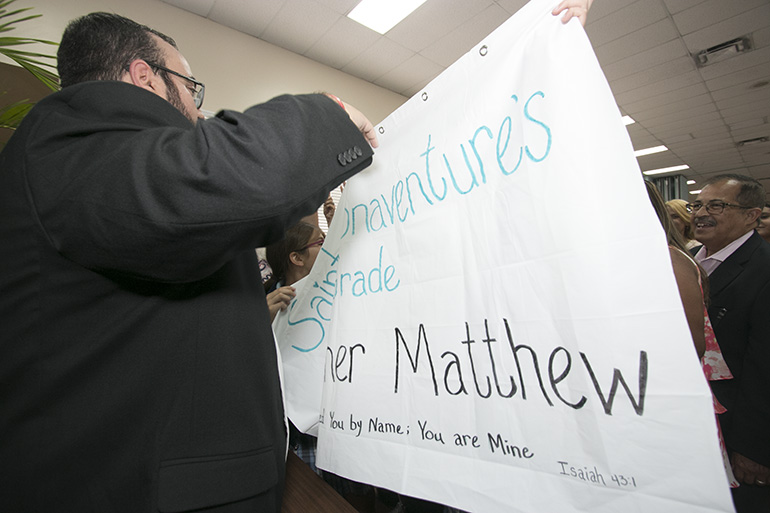 At the cathedral hall after the ceremony, Father Matthew Gomez exchanges