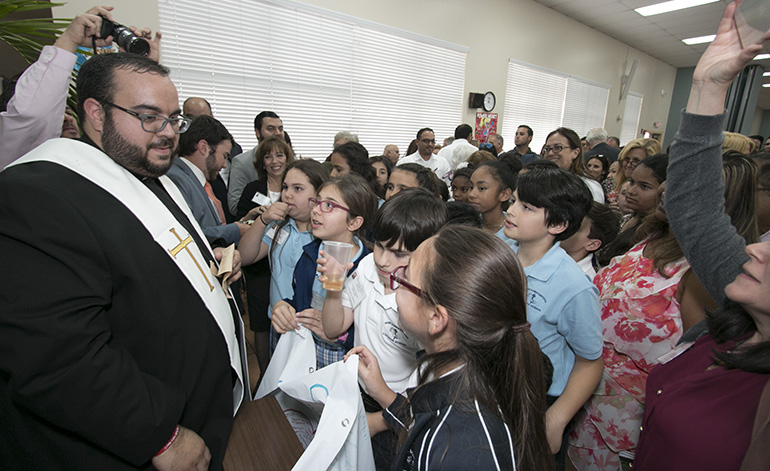 At the cathedral hall after the ceremony, Father Matthew Gomez speaks with fifth-graders from St. Bonaventure School in Davie, who