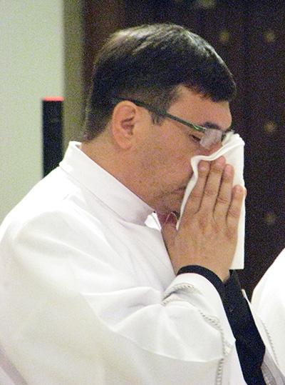 Emocionado el P. Omar Ayubi se limpia las lágrimas después de que el Arzobispo Thomas Wenski le impusiera las manos y lo ordenara