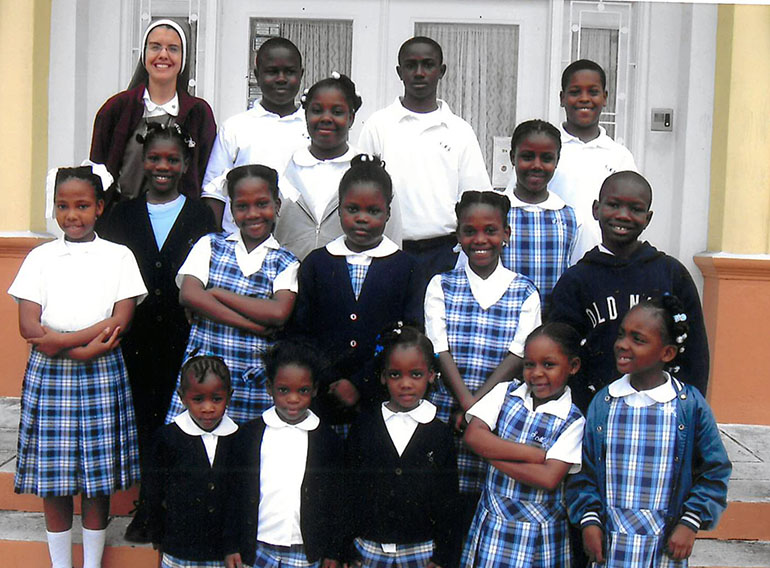 Younger days: A photo of Eudens (second row, from the bottom, far right), and Tajmara (third row, from the bottom, far left) with classmates from St. Mary Cathedral School who were also survivors of the earthquake in Haiti. Accompanying them is Principal Sister Michelle Fernandez, of the Servants of the Pierced Hearts of Jesus and Mary.