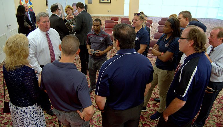 Sports program personnel flock around incoming St. Thomas University president David Armstrong, in white shirt and tie at left, after a Town Hall meeting June 4.