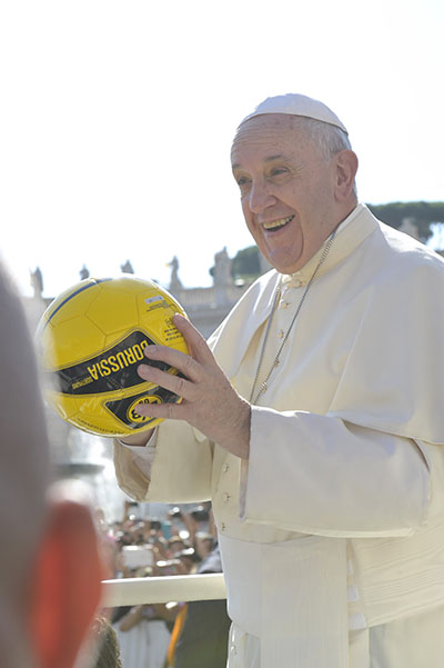 Pope Francis holds a soccer ball in St. Peter's Square during the Wednesday general audience on August 26, 2015.