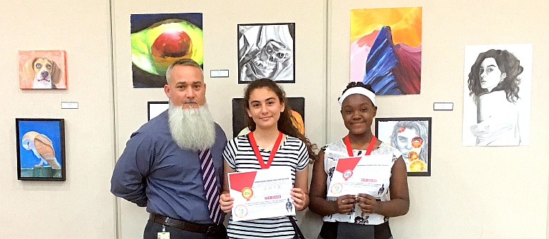 Two student artists show their awards during Pace High School's Gallery Night middle school competition. In the middle is Sarah Khoury of St. John the Apostle School, with Alexandra Creed of St. Bartholomew School on the right. At left is Marcel Navarro, lead instructor for Pace's Academy for Visual and Performing Arts.
