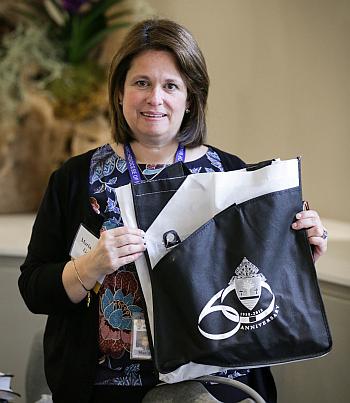 María Isabel García, de la Oficina de Culto, muestra una de las bolsas de regalo que se entregaron a los obispos asistentes a la reunión de primavera de la Conferencia de Obispos Católicos de los Estados Unidos, en Fort Lauderdale.