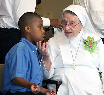 Sister Lucia Ceccotti chats with student Ahmad Williams, 9, at her 90th birthday celebration.