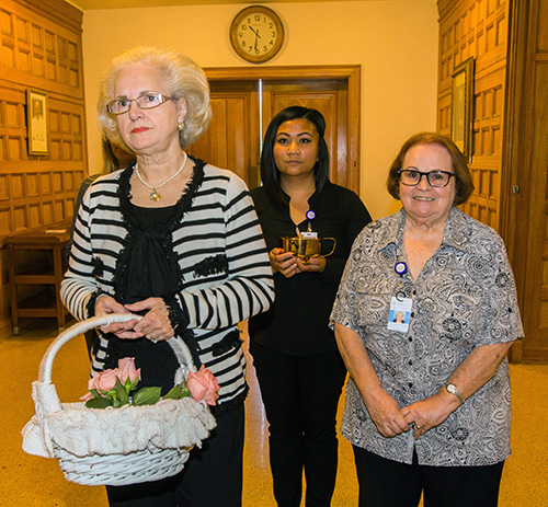 From left, Martha Rodriguez de Perez prepares to bring up the offertory with Catholic Hospice's Gian Santayana, center, bereavement coordinator, and Luz Suarez Macias, bereavement counselor.