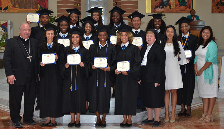 Graduates of Holy Family Academy and the Archdiocese of Miami Virtual Catholic School in the Turks and Caicos pose for a photo  with Bishop Peter Baldacchino, far left, Sister Elizabeth Worley of the Sisters of St. Joseph, archdiocesan chancellor and COO, as well as their 12th grade teacher and principal. The Turks and Caicos educational system provides education through the 11th grade. In order to qualify for U.S. universities, the students of Holy Family Academy complete their 12th grade via the ADOM Virtual School, gathering daily as a group at the academy's classrooms.  