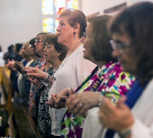Members of the Miami Archdiocesan Council of Catholic Women recite the Lord's Prayer during the Mass at St. James Church where the MACCW presented layettes to seven Haitian mothers.