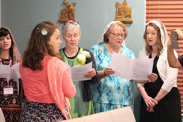 La cantante y directora de canto, Claire Halbur, vestida de rosado, dirige un pequeño coro de vírgenes consagradas durante la Misa del 8 de julio, en el Centro de Renovación MorningStar, en Pinecrest.