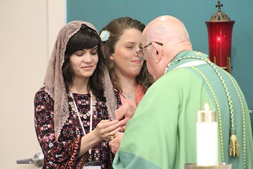 Elizabeth Rizzo, una virgen consagrada de Nueva Orleáns, recibe la Comunión del Arzobispo John Favalora. Junto a ella está Claire Halbur.