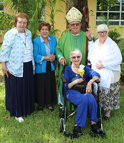 The consecrated virgins from the state of Florida pose with Archbishop Emeritus John Favalora; from left: Nancy Dvorak of the Diocese of St. Augustine, and Magalis Aguilera, Kathleen Danes (seated), and Maria de Los Angeles Exposito, all from the Archdiocese of Miami.