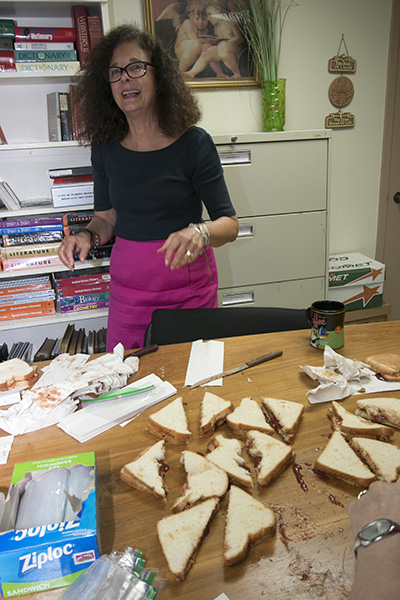 Kim Pryzbylski, superintendent of schools, does her job: cutting the peanut butter and jelly sandwiches into halves.