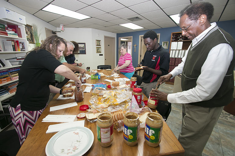 Busy assembling peanut butter sandwiches, from left: nt to back: Marcey Ayers, coordinator of special programs; Domenick Russo, coordinator of certification; Kim Pryzbylski, archdiocesan superintendent of schools; Hope Sadowski, administrative executive assistant; ADOM Virtual School student Samuel Ambroise; and Donald Edwards, associate superintendent of schools.