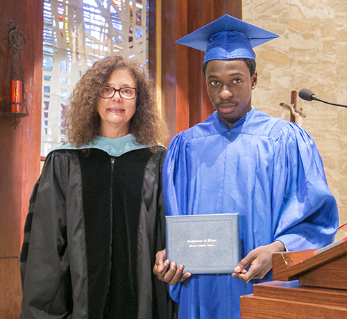 Samuel Ambroise, first local graduate of the Archdiocese of Miami Virtual Catholic School, receives his diploma from Superintendent Kim Pryzbylski.