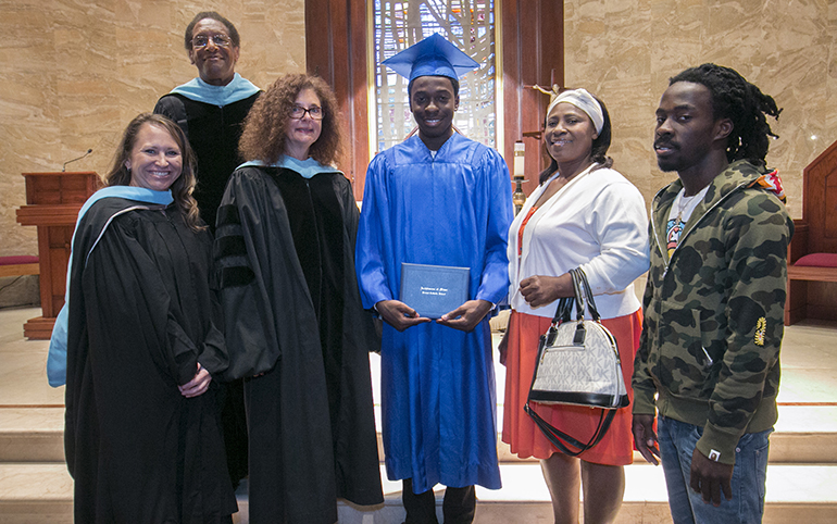 Samuel Ambroise, first local graduate of the Archdiocese of Miami Virtual Catholic School, poses with archdiocesan school officials and his family after his graduation Mass and ceremony; from left: Marcey Ayers, his virtual school teacher; Donald Edwards, associate superintendent; Kim Pryzbylski, superintendent; mother Ketty Ambroise and older brother Pekto.