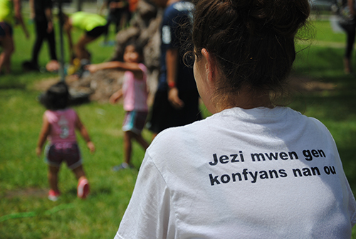 A volunteer watches activities on the the field. Her shirt reads in Haitian Creole,