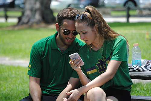 Among the participants at the Champions Challenge were married couples. Here, A.J. and Melissa Tablada, members of the Fiat marriage group for young adults, check their phone during a break.