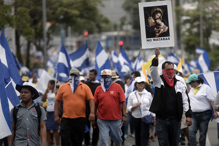 "Anti-government demonstrators hold a religious image reading ""You shall not kill"" as they take part in a pilgrimage in Managua on July 28, 2018. Thousands of Nicaraguans marched in support of the episcopate, accused by the government of being in favor of a coup, in the framework of protests which have been taking place since April and in which over 300 people were killed."