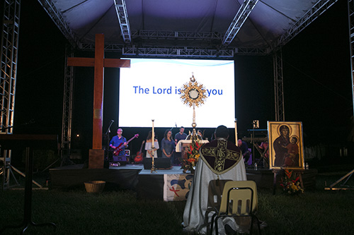Archbishop Jose Domingo Ulloa of Panama leads participants in prayer before the Blessed Sacrament during the Aug. 22 prayer vigil with the WYD cross and icon.