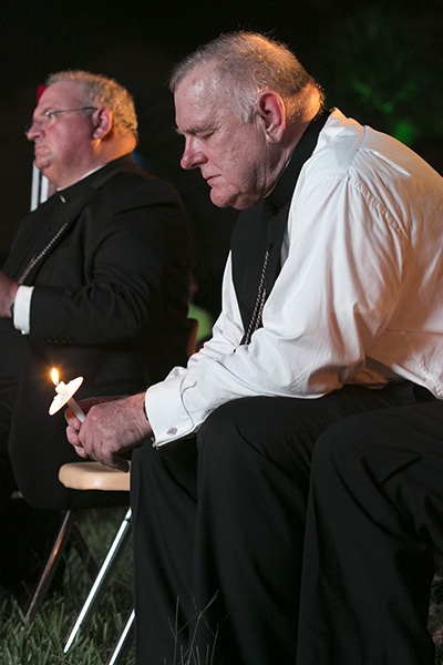 From left, Auxiliary Bishop Peter Baldacchino and Archbishop Thomas Wenski pray before the Blessed Sacrament at the Aug. 22 Wold Youth Day prayer vigil at St. John Vianney College Seminary.