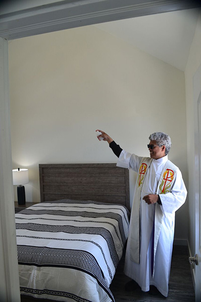 """Father Jets Medina, pastor of St. Peter Church in Big Pine Key, sprinkles holy water on the bedroom of the first of four """"Keys Cottages"""" that will provide affordable housing for area workers."""