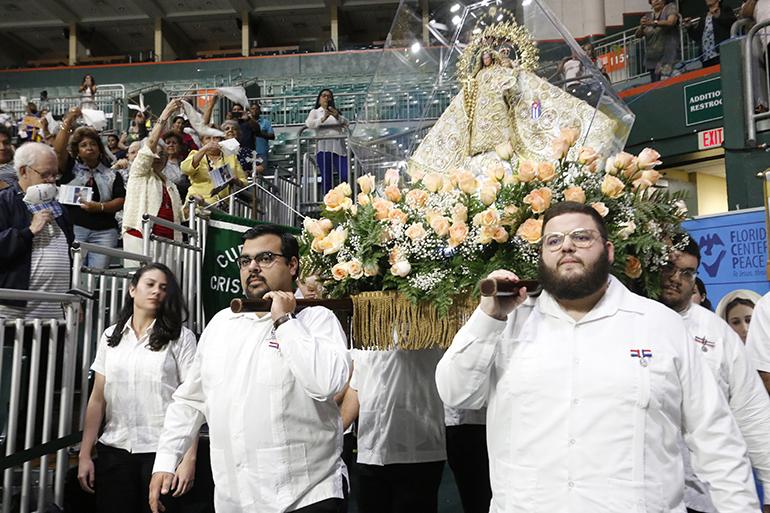 Los miembros de Encuentros Juveniles cargan la imagen de Nuestra Señora de la Caridad durante la procesión antes de la Misa en su día de fiesta.