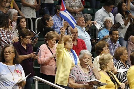 La gente agita banderas cubanas y pañuelos blancos mientras los miembros de Encuentros Juveniles llevan la imagen de Nuestra Señora de la Caridad alrededor del Watsco Center, antes de la Misa en su día de fiesta.
