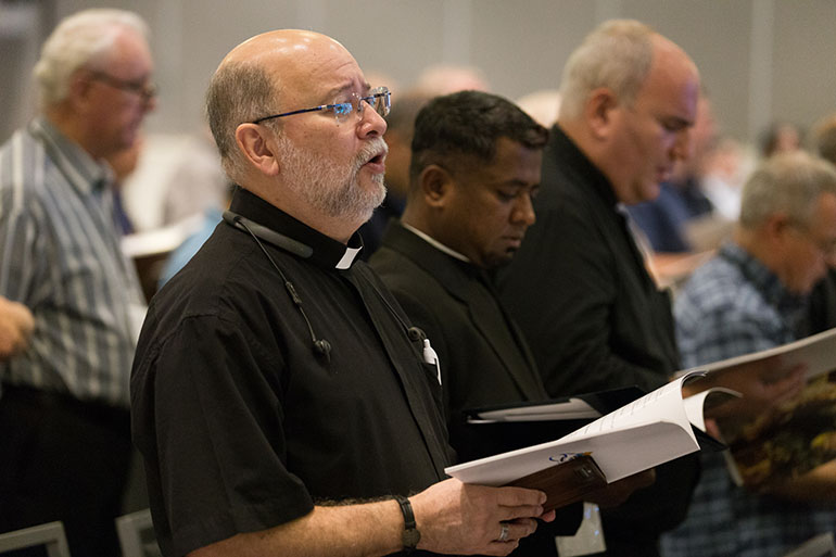 Archdiocesan priests sing evening prayers Sept. 18 at the opening of an annual clergy convocation being held at the Hilton Miami Downtown.