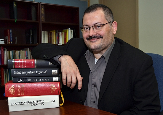 Gustavo Zayas, music director for the archdiocese, literally leans on historical guides in assessing music.