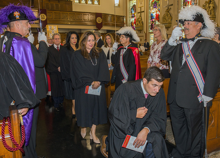 Circuit Court Judge Rodolfo Ruiz genuflects before the altar as Circuit Court Judges Monica Gordo, Beatrice Butchko and John Thornton walk behind him and Knights of Columbus Council 3201 honor guard line the aisle.