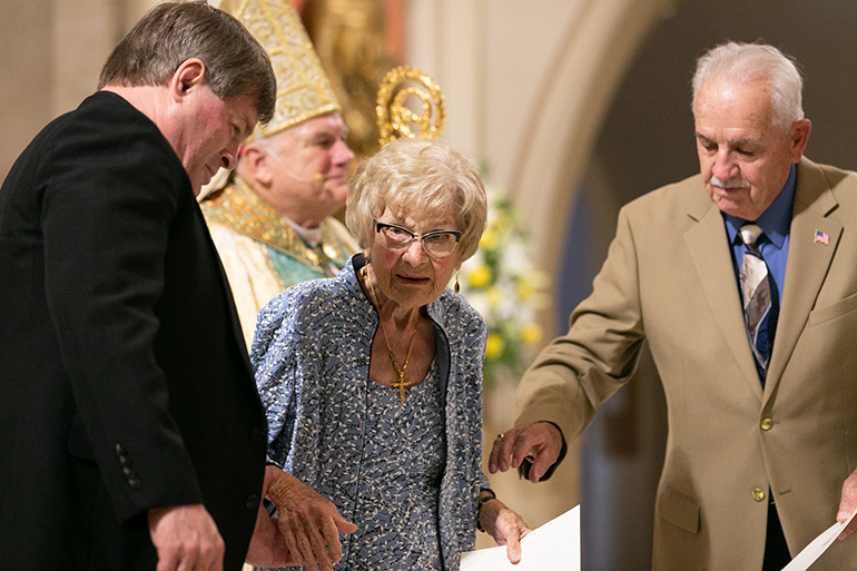 Rose Preseau, 101, leaves the sanctuary after being greeted by Archbishop Thomas Wenski. She is accompanied by fellow Jubilaeum honoree John Frink and her pastor, Father Steve O'Hala.