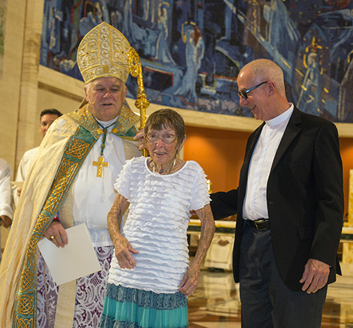 Archbishop Thomas Wenski gives Maryann Don of San Pablo Parish in Marathon the Jubilaeum pin her pastor, Father Luis Perez, stands beside her.