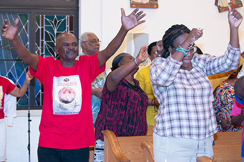 Jules Verme, far left, joins others in praying and swaying to the music during Jericho 2018 at Notre Dame d'Haiti Mission in Miami.
