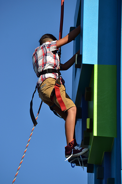 Gustavo Avila, 9, tackles a climbing wall during the archdiocese's 60th anniversary picnic at Nativity Church in Hollywood.