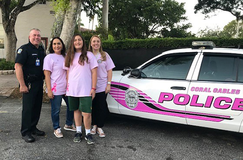 From left: Officer Robert Alonso of the Coral Gables Police Department with Monica Cejas, Anabelle Cejas and Cristina Guanche-Martinez pose with the Breast Cancer Awareness Pink Police Car.