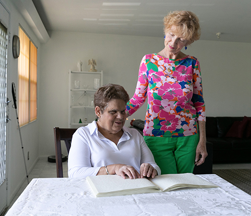 Coconut Creek resident Lygia Bohan, seated, who attends All Saints Parish in Sunrise, reads Catholic materials in braille, including the Sunday Mass readings which she reviews in advance of attending church. With her is Lighthouse Point resident and longtime disabilities advocate Dolores Hanley McDiarmid, who attends St. John the Baptist Church in Fort Lauderdale.
